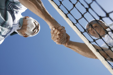 Senior men shaking hands over tennis net, view from below
