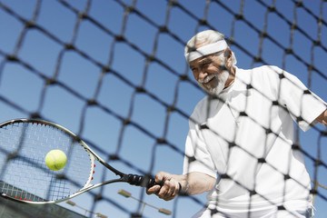 Senior man hitting tennis ball forehand near tennis net