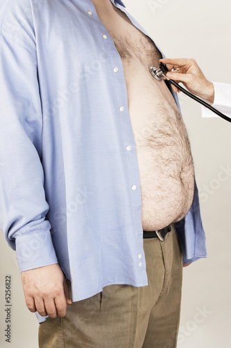 Doctor hand with stethoscope on overweight man's heart, side view, mid section