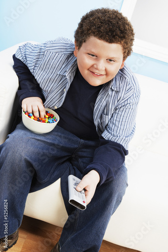 Overweight boy 13-15 Eating Junk Food, holding remote control