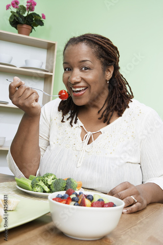 Overweight woman eating healthy food, portrait