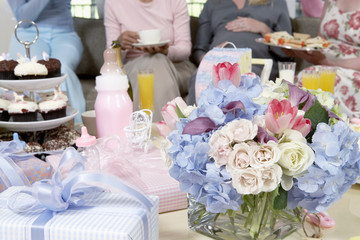 Table of gifts, flowers and cakes at baby shower