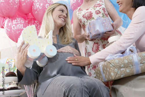 Friends giving gifts to woman at baby shower