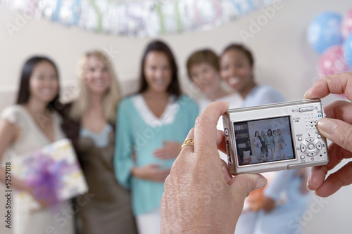 Woman taking photo of friends at baby shower, focus on camera