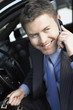 Businessman Using mobile Phone in car, smiling, half-length