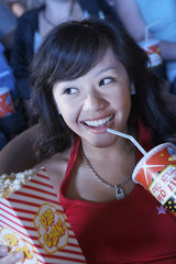 Young Woman Drinking Soda, Watching Movie in movie theatre
