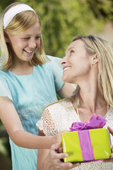 Girl standing behind mother, giving gift. Mother looking over shoulder, smiling