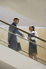 Businessman and Businesswoman shaking hands on Escalator