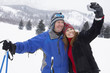 Couple on skis, photographing selves using digital camera, in snow covered field