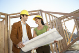 Couple in front of house being built