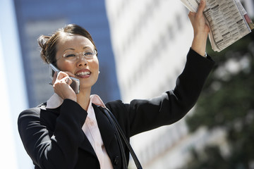 Businesswoman Hailing Cab using Cell Phone