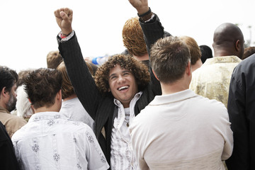 Cheering man facing the other way to rest of crowd