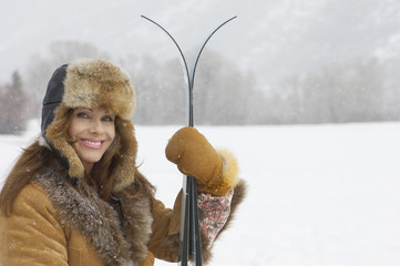 Woman wearing fur coat and hat, holding skis, in snow covered field, portrait.