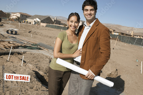 Couple by plot of land for new home