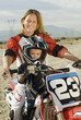 Mother and son 3-4 on motocross bike in desert, portrait