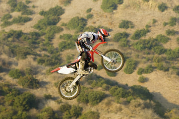 Motocross racer in mid-air over desert