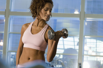 Young woman using dumbbell in gymnasium