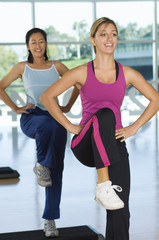 Two women in step aerobics class