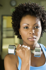 Woman using dumbbell indoors, close-up, portrait