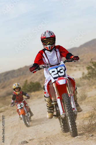 Mother and son 5-6 on motocross bikes in desert