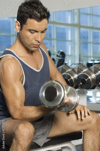 Man using dumbbell in gymnasium