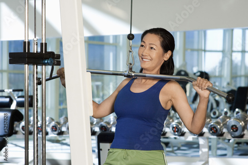 Woman using exercise equipment in gymnasium