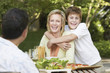 Family eating meal outside, son hugging mother