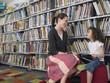 Elementary Student With Teacher in Library
