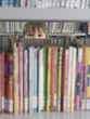 Boy peeking from behind bookshelf in library