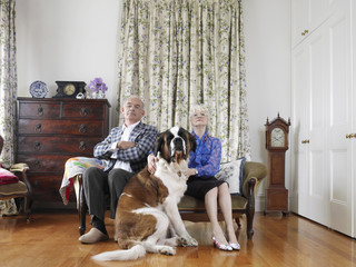 Senior couple posing in living room with dog