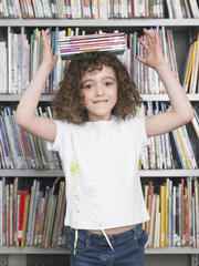 Girl balancing stack of books on head in library, portrait