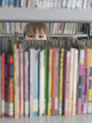 Boy peeking from behind bookshelf in library