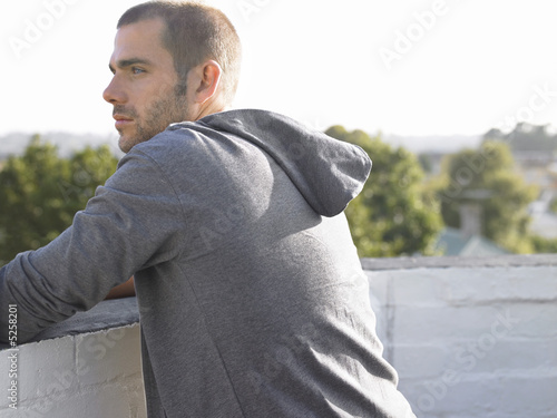 Man looking over balcony half length