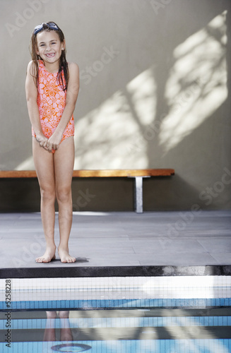 Girl standing on edge of pool, portrait