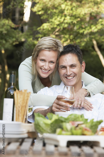 Couple embracing at outdoor table, portrait