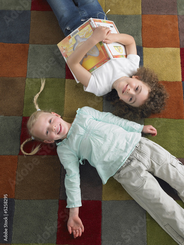 Two girls lying down on library floor, view from above