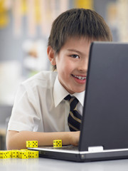 Elementary schoolboy using laptop sitting in classroom