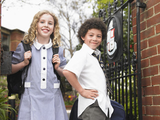 Two elementary students standing at school gate, portrait