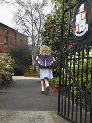 Elementary schoolgirl walking towards school building, back view