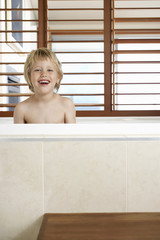 Smiling Boy sitting in Bathtub