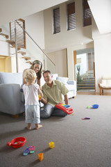 Parents sitting in living room, watching son Playing with toys