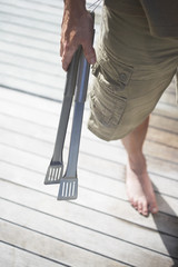 Man in shorts Holding Tongs on wooden porch, low section, high angle view