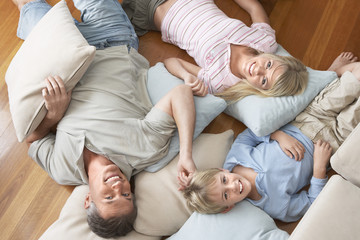 Father and Children Lying on pillows and cushions on wood Floor, overhead view