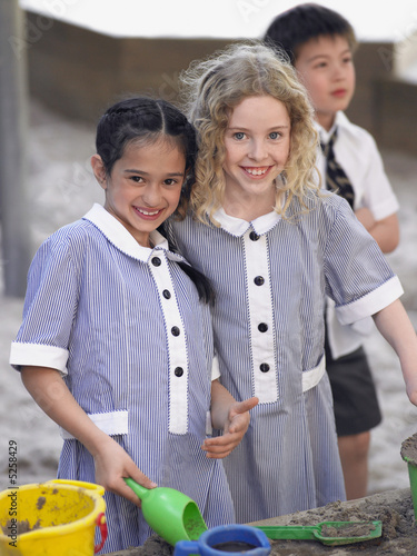 Two school girls playing in playground, portrait