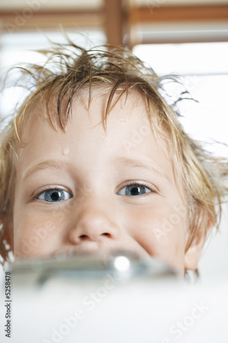 Boy with messy, wet hair, looking over edge of  Bathtub, close-up