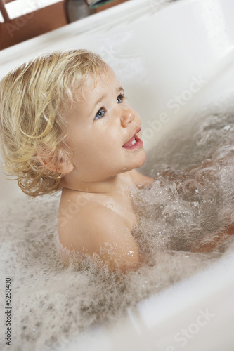 Baby Boy sitting in a bubble-filled Bathtub, side view