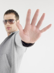 Man in sunglasses viewed past extended hand
