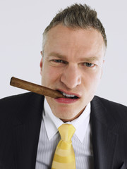 Businessman smoking cigar in studio