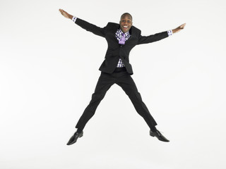 Man in suit jumping in star shape in studio