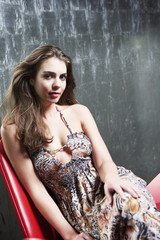 Stylish Young Woman sitting in stylized chair, legs crossed, in metal room, portrait